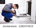 young repairman fixing... | Shutterstock . vector #1282474513