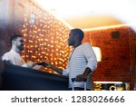 Stock photo young african american traveler consulting with hotel receptionist by counter during accommodation 1283026666
