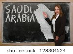 Successful, beautiful and confident young woman showing map of saudi arabia on blackboard for presentation, marketing research and tourist advertising - stock photo