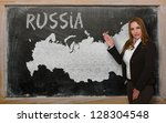 Successful, beautiful and confident young woman showing map of russia on blackboard for presentation, marketing research and tourist advertising - stock photo