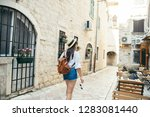 woman walking by tight streets... | Shutterstock . vector #1283081440