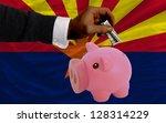 man putting dollar into piggy... | Shutterstock . vector #128314229