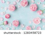 Stock photo beautiful rose flowers and petals on blue background greeting card for womens day or mothers day 1283458723