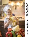 little girl cuts fruit in... | Shutterstock . vector #1283470540