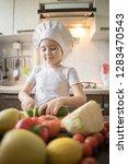little girl cuts fruit in... | Shutterstock . vector #1283470543