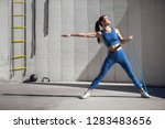 Female athlete uses stretch band to strengthen arms and core muscles, copy space