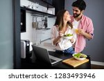 happy couple using laptop while ... | Shutterstock . vector #1283493946