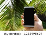 phone in hand in tropical nature | Shutterstock . vector #1283495629