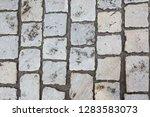wet cobbled stone sidewalk...   Shutterstock . vector #1283583073