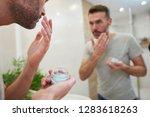 man applying beauty product in... | Shutterstock . vector #1283618263