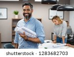 Small photo of Portrait of multiethnic architect with blueprints in creative office. Mature middle eastern contractor holding roll of architectural projects while looking at camera. Happy latin man in casual.