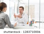 mid adult manager discussing...   Shutterstock . vector #1283710006