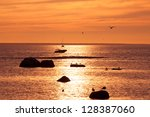 Yachts near the island on the golden sunrise over the sea - stock photo