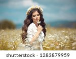 Small photo of Beautiful young girl with flower enjoying in chamomile field. Carefree happy brunette woman with chaplet on healthy wavy hair having fun outdoor in nature. People freedom style.