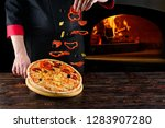 chef prepares pizza levitation... | Shutterstock . vector #1283907280