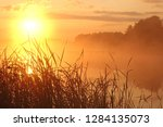 hazy lake at sunrise  | Shutterstock . vector #1284135073