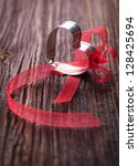 heart with red bow on wooden background - stock photo