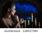 Indoors portrait of a sorceress with the glass sphere and the candles - stock photo