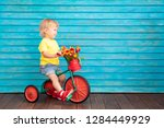 funny child riding bike. happy... | Shutterstock . vector #1284449929