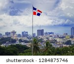 flag of the Dominican Republic on the background of the panorama of Santa Domingo and thunderclouds
