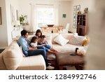 young hispanic family sitting...   Shutterstock . vector #1284992746