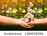 man and woman hand hold a home... | Shutterstock . vector #1285018396