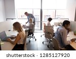Small photo of Five different multi-ethnic employees sitting at shared desk in modern light cozy coworking space working using computers having busy workday. Corporate teamwork common aim every day routine concept