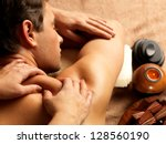 masseur doing massage on man... | Shutterstock . vector #128560190