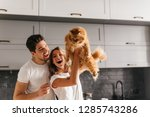 Stock photo good humoured couple playing with pet in kitchen relaxed girl holding fluffy cat with smile 1285743286