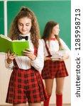 schoolgirl looking into a book... | Shutterstock . vector #1285958713