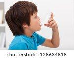 Boy using inhaler - respiratory system illness - stock photo