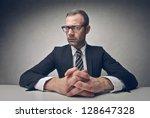 serious businessman sitting at...   Shutterstock . vector #128647328