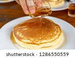 drop syrup on the pancake on... | Shutterstock . vector #1286550559