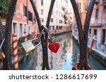 Combination red heart-shaped and other padlocks on the bridge in Venice, Italy. Sunny day, historical buildings and the canal in the background. Close up. Valentine