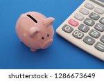 piggy bank and calculator on... | Shutterstock . vector #1286673649