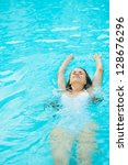 young woman swimming in pool | Shutterstock . vector #128676296