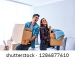 Small photo of New Home. Funny young couple enjoy and celebrating moving to new home. Happy couple at empty room of new home. Happy couple is having fun with cardboard boxes in new house at moving day.