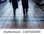 two soldiers in black overcoats marching on the pavement