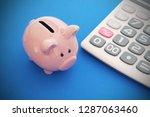 piggy bank and calculator on... | Shutterstock . vector #1287063460