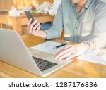 a women using phone on laptop... | Shutterstock . vector #1287176836