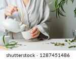 female hands pouring tea from... | Shutterstock . vector #1287451486