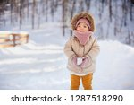adorable baby girl in a warm... | Shutterstock . vector #1287518290