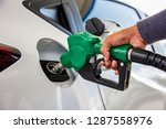 Stock photo man handle pumping gasoline fuel nozzle to refuel vehicle fueling facility at petrol station white 1287558976
