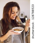 smiling woman enjoying her bowl ... | Shutterstock . vector #128788523