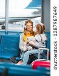 attractive mother in headphones ... | Shutterstock . vector #1287987649