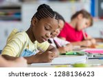 Stock photo cute pupil writing at desk in classroom at the elementary school student girl doing test in 1288136623