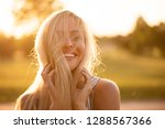 Stock photo smiling shy woman poses while holding her hair 1288567366