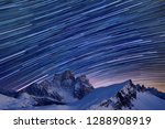 Star trails over the mountains, Dolomites, Italy.  Beautiful spiral star trail at night. Fantastic star timelapse with mountain background.