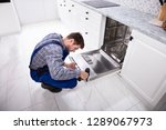 young repairman fixing... | Shutterstock . vector #1289067973