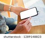 phone in hand s women on wooden ... | Shutterstock . vector #1289148823